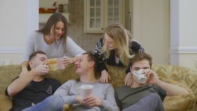 Grupa młodzi caucasian ludzie relaksuje na kanapie w domu i pijący kawę zbiory