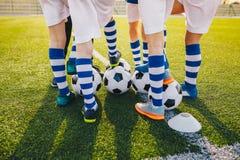 Grupa młodzi gracz futbolu na piłki nożnej szkoleniu Nogi piłka nożna żartują kopanie piłki na polu obrazy stock