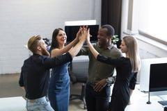 Grupa młodzi koledzy daje each inny wysocy pięć zdjęcie royalty free