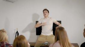 Grupa młodzi ludzie bawić się szarady w mieszkaniu, śmieszny mężczyzna pokazuje wizerunki i inny zgadywa zdjęcie wideo