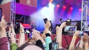 Grupa młodzi ludzie Cieszy się Plenerowego festiwal muzyki Zakończenie tylni widok tłum na koncercie Śmieszni ludzie strzelają a zdjęcie wideo