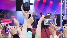 Grupa młodzi ludzie Cieszy się Plenerowego festiwal muzyki Zakończenie tylni widok tłum na koncercie Śmieszni ludzie strzelają a zbiory