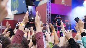 Grupa młodzi ludzie Cieszy się Plenerowego festiwal muzyki Zakończenie tylni widok tłum na koncercie Śmieszni ludzie strzelają a zdjęcie stock