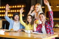 Grupa młodzi ludzie ma zabawę w kawiarni obraz royalty free