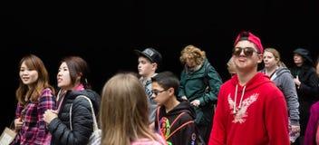 Grupa młodzi ludzie przeciw czerni ścianie Fotografia Royalty Free