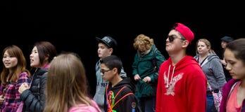 Grupa młodzi ludzie przeciw czerni ścianie Fotografia Stock