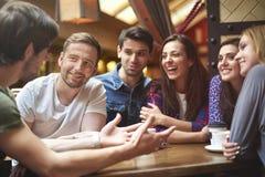 Grupa młodzi ludzie przy kawiarnią Zdjęcia Royalty Free