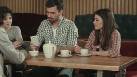 Grupa młodzi ludzie siedzi przy cukiernianym, opowiada herbaty i pije, zdjęcie wideo