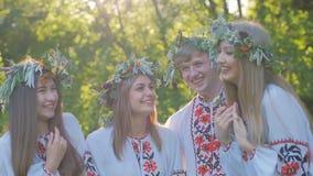 Grupa młodzi ludzie w krajowych kostiumach Slawistycznych świętuje lata solstice Grupa dziewczyny i chłopiec opowiada i zbiory wideo