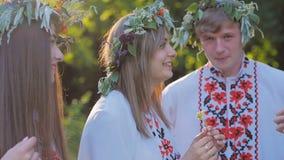 Grupa młodzi ludzie w krajowych kostiumach Slawistycznych świętuje lata solstice Grupa dziewczyny i chłopiec opowiada i zdjęcie wideo