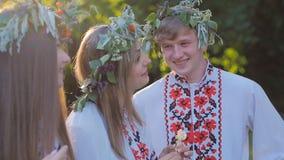 Grupa młodzi ludzie w krajowych kostiumach Slawistycznych świętuje lata solstice Grupa dziewczyny i chłopiec opowiada i zbiory