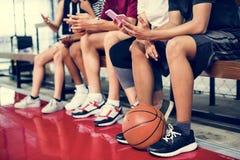 Grupa młodzi nastolatków przyjaciele na boisko do koszykówki relaksuje używać smartphone nałogu pojęcie zdjęcie stock