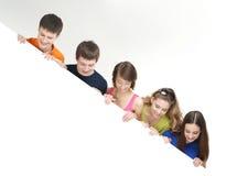 Grupa młodzi nastolatkowie trzyma białego sztandar zdjęcia stock