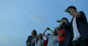 Grupa młodzi przyjaciele świętuje z grzanką i clinking podnoszący szkło przy lato dachem bawi się zdjęcie wideo