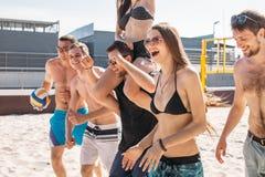 Grupa młodzi przyjaciele chodzi na plażowej siatkówki sądzie zdjęcia stock