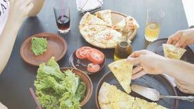 Grupa młodzi przyjaciele je pizzę w plenerowym zbiory