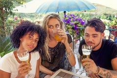 Grupa młodzi przyjaciele je przekąski i pić Zdjęcia Stock