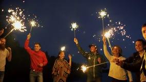 Grupa młodzi przyjaciele ma wyrzucać na brzeg przyjęcia Przyjaciele tanczy i świętuje z sparklers w mrocznym zmierzchu zbiory wideo