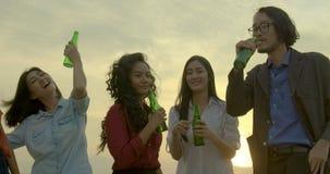 Grupa młodzi przyjaciele tanczy zabawę i ma świętuje z grzanką i clinking podnoszący szkło przy lato dachem bawi się zdjęcie wideo