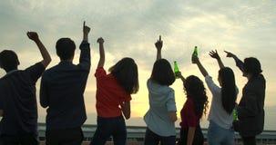 Grupa młodzi przyjaciele tanczy zabawę i ma świętuje z grzanką i clinking podnoszący szkło przy lato dachem bawi się zbiory