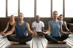 Grupa młodzi sporty ludzie siedzi w Sukhasana ćwiczeniu Obraz Royalty Free