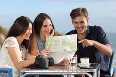 Grupa młodzi turystyczni przyjaciele konsultuje papierową mapę obraz royalty free
