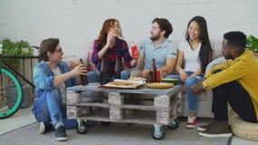 Grupa młodzi wieloetniczni przyjaciele opowiada wpólnie i zabawę podczas gdy mieć domowego przyjęcia indoors cieszy się przekąski zbiory