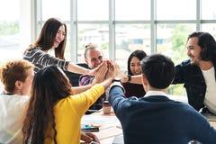 Grupa młodzi wieloetniczni różnorodni ludzie gestykuluje rękę pięć, roześmiany przy biurem i ono uśmiecha się wpólnie w brainstor fotografia stock
