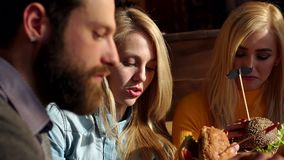 Grupa m?odzi i rozochoceni przyjaciele je wy?mienicie hamburgery w modnej kawiarni zdjęcie wideo