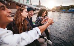 Grupa młodzi ludzie ma napoje przy jeziorem Obraz Stock