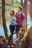 Grupa m?odzi przyjaciele wycieczkuje przez lasu z rowerami na pi?knym letnim dniu fotografia royalty free