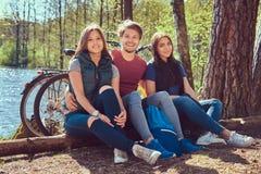 Grupa m?odzi przyjaciele wycieczkuje przez lasu z rowerami na pi?knym letnim dniu fotografia stock