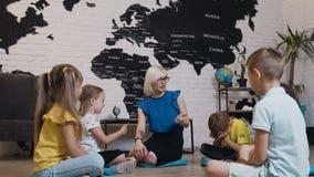 Grupa mali ucznie od pięć dzieci siedzi na podłoga i słuchaniu nauczyciel Dzieci i edukacja, młoda blondynka zbiory