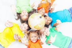 Grupa międzynarodowi śmieszni dzieciaki z kuli ziemskiej ziemią Fotografia Royalty Free