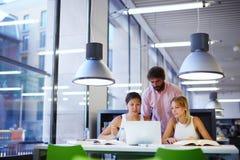 Grupa międzynarodowi studenci uniwersytetu uczy się w bibliotece