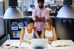Grupa międzynarodowi studenci uniwersytetu uczy się z książkami i laptopem w bibliotece Obrazy Stock