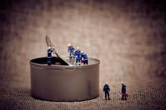 Grupa miniaturowi pracownicy otwiera puszkę Koloru brzmienie nastrajający makro- Zdjęcie Stock