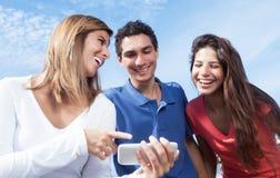 Grupa młodzi ludzie pokazuje obrazki przy telefonem Obraz Royalty Free