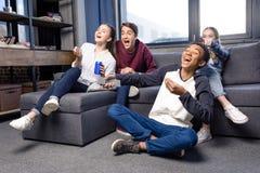 Grupa nastolatkowie ogląda film wpólnie w domu, nastolatkowie ma zabawy pojęcie zdjęcie royalty free
