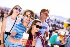 Grupa nastolatkowie przy lato festiwalem muzyki, słoneczny dzień Zdjęcia Stock