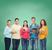 Grupa nastolatkowie z smartphones i pastylka komputerem osobistym Zdjęcia Stock