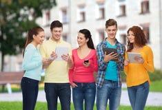 Grupa nastolatkowie z smartphones i pastylka komputerem osobistym Zdjęcie Stock