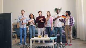 Grupa niemiec wachluje mężczyzn i kobiety śpiewa hymnu falowanie zaznaczają oglądać TV zdjęcie wideo