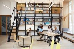Grupa partnery biznesowi na spotkaniu dyskutuje firmy zyskuje, robić badaniu, patrzeje przez ompetieour ` s pracy dalej obrazy stock