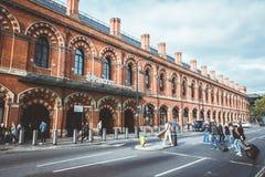 Grupa pasażery lub podróżnicy krzyżujemy ulicę przed królewiątka St Pancras Przecinającą stacją fotografia stock