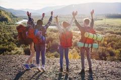Grupa pięć szczęśliwych przyjaciół skacze przy zmierzchu czasem na tło górach zdjęcia royalty free