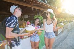 Grupa Pije koks Na Tajlandia Ulicznym rynku, Rozochoconym mężczyzna I kobietach W Tradycyjnych owoc turyści Opowiada, Zdjęcie Royalty Free