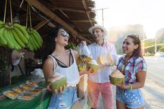 Grupa Pije koks Na Tajlandia Ulicznym rynku, Rozochoconym mężczyzna I kobietach W Tradycyjnych owoc turyści Opowiada, Fotografia Royalty Free