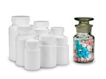 Grupa plastikowe małe butelki przeciw szklanej buteleczce z pigułkami. Fotografia Royalty Free