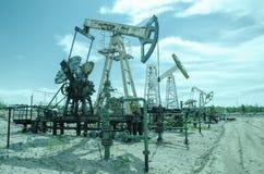 Grupa pompowa dźwigarka i wellhead w polu naftowym obraz stock